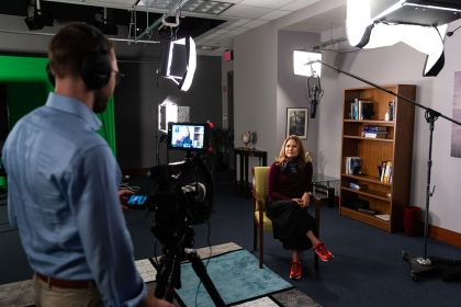 Professor Ariadna Pichs in a studio sitting in a chair under lights while a videographer films